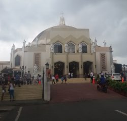 The facade of Antipolo Cathedral is made of various shades of beige and brown. Its structure is rectangular, as seen from the front with a hemispherical dome on top. The front side has three main entrances, and above these doors are three glass windows with a shape of a house-like pentagon. White statues of saints are standing atop the rectangular structure as if they are surrounding the dome on their back. Two letter Ms intersecting at the right angle is on top of the dome, and a white cross on top of Ms.