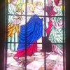 A tall stained glass pane depicts the Fourth Joyful Mystery of the Rosary, the Presentation of Jesus at the Temple. Mary is wearing blue and red clothing and white headcover. Joseph is wearing green and goldtone clothing. Mary is carrying baby Jesus wrapped in white cloth and looks like she is passing him to a man with red clothing and headdress, possibly a Jewish priest. There is also a woman on the right beside the priest wearing green and pink. Another man with white headdress and yellow clothing stands behind the woman. They are on the steps of what looks like a temple, with two pillars, a window, and a red curtain visible in the background.