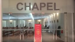The chapel inside the Ayala Malls Capitol Central is a simple room with glass walls and doors through which the interior can be seen. The chapel has white walls, brown floor, and several rows of wooden pew.