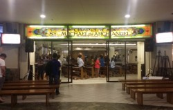 Chapel of St. Michael the Archangel at Trinoma as seen from outside. Several people attend the mass, the doors are open, and there are sits placed outside.