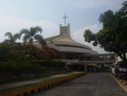 The Christ the King Parish in Greenmeadows, Quezon City, has the appearance of two white concrete slightly-thickened discs formed by the ceiling and the external veranda. There's a gap between the discs through which you can see the wall and the glass doors. On top of the upper disc is a green conical roof with a hollow rectangular structure on top; a cross is mounted on top of this structure. A bridge is also seen in this picture connecting the church to a building across the driveway.