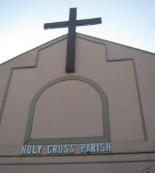 Upper part of the structure of Parish of the Holy Cross. It is colored pink and has cross on top and the words HOLY CROSS PARISH in metallic letters.