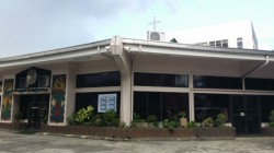 The structure of Holy Family Parish is like a large bungalow and semicircle when viewed on top. It has a small cross and a taller building at the back. It is predominantly white but has black grill windows and gates.
