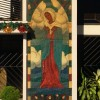 A glass mosaic of Mary on the side of the main entrance of the Holy Family Parish shows her crossing her arms above her chest. She is wearing a maroon robe with a blue overlay, and a white cover on her head.