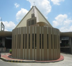 The frontage of Our Lady of Perpetual Help Parish along Jersey St. It has a triangular hat-like brown roof. The small structure with light on a pole on top in front is the new adoration chapel.