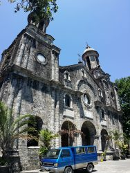 The front of San Sebastian Cathedral as seen from the corner of its yard. It has gray facade and has two towers on the sides. The curvature of the towers is due to vertical panorama shot; they are actually straight. It has several semi-oblong windows and also a semi-oblong main entrance at the center and ground level. Above the main entrance is a circular cavity with what looks like a white statue of Jesus inside. The central structure between the bell towers has a triangular roof with a cross on top. The bell towers also have crosses on top and circular windows below the bell structures.