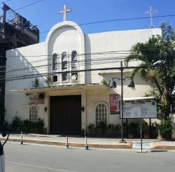 This is the frontage of Santisima Trinidad Parish along Estrada St. It has white facade with semi-oblong arc in the middle. A cross is on top of the semi-oblong and below it is the brown rectangular main entrance. The ground on both sides of the entrance is decorated with potted plants.