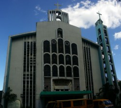 The facade of San Isidro Labrador Parish is mostly white with cyan highlights. It has two crosses, one on the top center and the other on the right (if you are facing the church) on top of a thinner cyan bell tower. The church has twelve semi-oblong windows on the central protrusion and several rectangle windows on both sides.