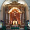 The altar of Sto. Rosario Parish in Pasig shows a crucifix in an arch-like structure with pillars on the left and on the right. There is an angel on top of each of the two pillars. Above the crucifix is a dove enclosed by sun-like ornament and below it is the tabernacle. The color of the crucifix and the surrounding structure is mostly maroon and gold, while the altar is covered with a green cloth.