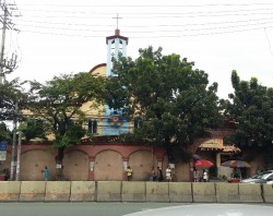 The Sto. Rosario Parish as seen from the opposite side of Ortigas Avenue. The church is mostly yellow with maroon roof and blue bell tower at the center. The church structure is covered by a salmon pink-colored wall with a large gate on the right side. Trees grow in front of the church, and their thick bush further covers the church building.