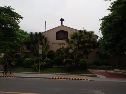 The Saint John Paul II Parish is a low-rise structure with a beige exterior, low triangular roof, and a simple black cross on top. Several plants surround it. A lawn with grasses separates the church entrance from the sidewalk. A red curve path between the lawn and the entrance allows cars to stop and drop passengers to the church without disturbing the vehicles on the main road. The angle of this shot allows us to see very little of the roof's surface, which is red, the same as that roof over a walk path behind the lawn on the left. A house-shape pentagon glass panel is in front of the church wall below the cross and above the main entrance; it is a stained glass window depiction of the Holy Family.