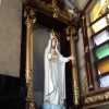 A statue of Mary showing her Immaculate Heart. Here, Mary is wearing white, with her arms and hands partially stretched outward. She is standing on what looks like a bluish white cloud. On her sides are pillars that are gold in color, with the top and bottom of the pillars being maroon with gold-colored decorations. The overhead above the stature is also maroon with gold decorations and smaller statues of angels sitting on top of the pillars.