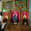 A gold-tone shelf with three panels contains statues and flowers on their feet. The one at the middle is the largest depicting Mary in pink robe, blue cloak, and white hood. The ones on the side are smaller. On the left is Jesus holding a lamb with both arms while tucking a brown staff on his elbow. I do not know who is this saint on the right: she is wearing a brown robe and cape and holding what looks like a monstrance. Above the shelf are portraits of St. Luke and St. John. St. Luke is holding a scroll with both hands, and a winged bull is partly visible on his left. St. John is holding a scroll with his right hand while letting its other end dangle; a while eagle is partly visible on his left.