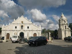 The frontage of the Vigan Cathedral is that of a white concrete on the shape of a house-like pentagon. The slanted sides are slightly curved inward. It has four spires evenly distributed on top and a black cross on the very top where the slanted segments meet. On the ground level, it has three semi-oblong entrances. The door at the center is open and slightly larger, while the ones on the sides are of the same size and are closed by brown wooden doors. Also seen in this picture is a separate bell tower structure on the right with the same color as the church's frontage. The bell tower has a dove statue on top, a clock near the top, two tiers with semi-oblong windows each, and a wider base with spires on four corners of its top surrounding the lower tier.
